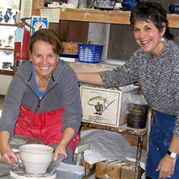 Instructor Hedy Hale helping beginning pottery student throwin on the wheel, including slab, coil, pinching, scultping for Raku firing using stoneware high fire clay