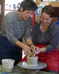Hedy helping pottery student throw on the potters wheel at full moon stdio working on ceramic piece - high fire stoneware clay